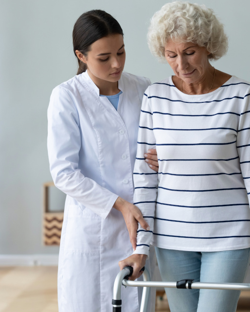 Young woman caregiver helping disabled old grandma patient using walker